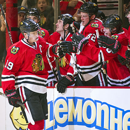 Chicago's Jonathan Toews (left) is congratulated by his teammates after scoring in the shootout. (AP)