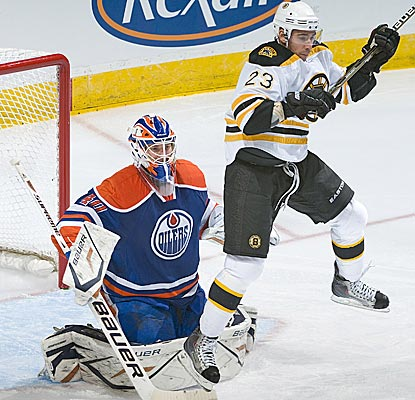 Chris Kelly jumps while screening the Oilers' Devan Dubnyk as the Bruins pick up another road win. (Getty Images)