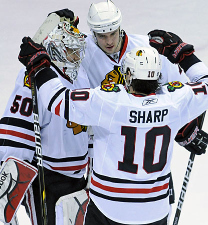Patrick Sharp and Duncan Keith congratulate Corey Crawford (left) after the 4-2 win. (AP)