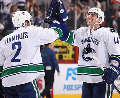 Alexandre Burrows, who misses a penalty shot in overtime, thanks Dan Hamhuis for picking him up with the winning goal. (Getty Images)