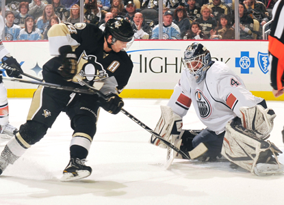 Chris Kunitz slips the puck past Oilers goalie Devan Dubnyk for the first of his two goals in the Penguins' win. (Getty Images)