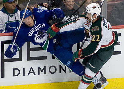 The Wild don't win, but Cal Clutterbuck still gets some satisfaction as he sends the Canucks' Christian Ehrhoff to the wall. (AP)