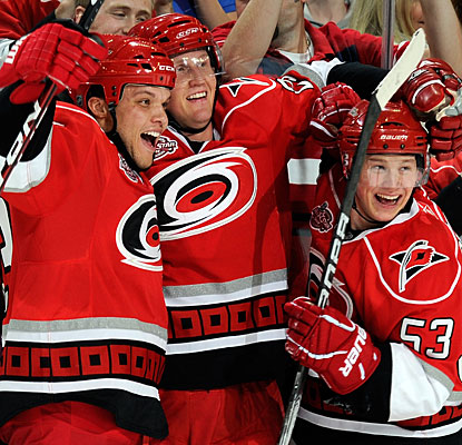 Joni Pitkanen (left) celebrates his winner with Derek Joslin and Jeff Skinner (53), who earlier nets his 25th goal. (Getty Images)
