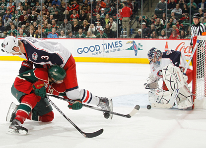 Marc Methot of the Blue Jackets collides with Matt Cullen of the Wild as Mathieu Garon makes one of 32 stops in goal. (Getty Images)