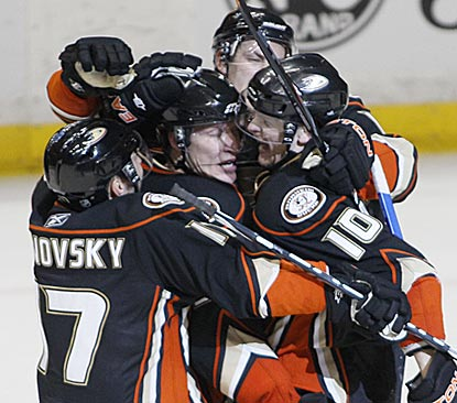 Corey Perry (10) joins Anaheim's group hug after his overtime goal caps a wild victory against Calgary.  (AP)