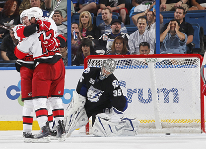 The Hurricanes celebrate one of Erik Cole's two goals as Lightning goalie Dwayne Rolson slumps in disappointment. (Getty Images)