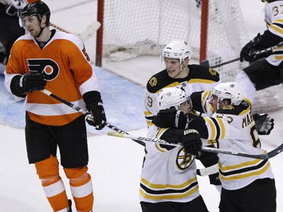 Boston's Brad Marchand (right) celebrates with teammates after scoring the eventual game winner against the Flyers. (AP)