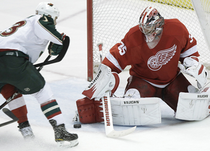 Red Wings goalie Jimmy Howard puts the stop on Eric Nystrom en route to making 27 saves in the win. (AP)