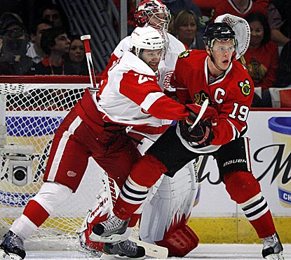 Chicago captain Jonathan Toews tries to create trouble in front of Red Wings goalie Jimmy Howard.  (AP)