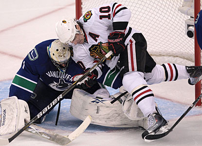 Roberto Luongo toughs it out and stands his crease as Chicago's Patrick Sharp crashes into the goalie. (AP)
