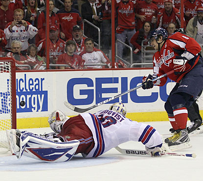 Alex Ovechkin, who has an assist, comes close to scoring a goal, too, but Henrik Lundqvist gets a piece of the puck. (Getty Images)