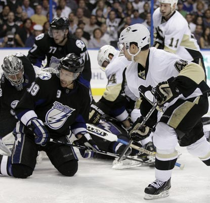 Tyler Kennedy (right) fires the puck past Lightning goalie Dwayne Roloson early in the third period of Game 3. (AP)