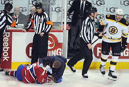 Milan Lucic (right) is escorted off the ice after being tossed for a nasty boarding hit on Jaroslav Spacek. (AP)