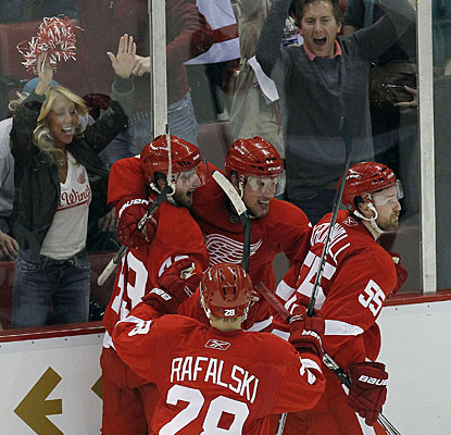 Darren Helm (center), teammates and fans alike are happy after Detroit pulls out the win. (US Presswire)
