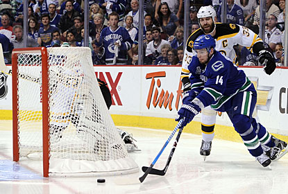 Alex Burrows takes advantage of an out-of-position Tim Thomas to put the puck in the net on a wraparound. (Getty Images)