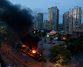 Police cars are set on fire, windows smashed and much more destruction on the streets of Vancouver. (AP)