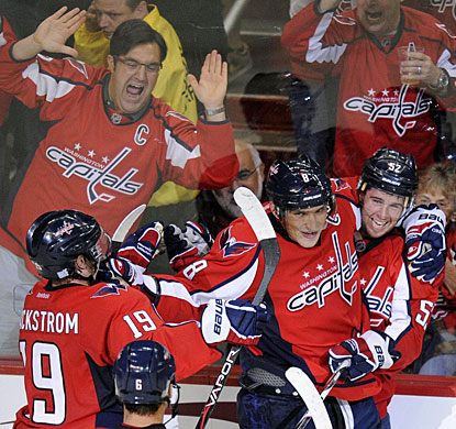 Mike Green (right) celebrates his overtime goal with Alexander Ovechkin and Nicklas Backstrom as fans also enjoy it. (AP)