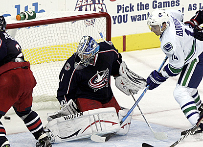 Alexandre Burrows (right) scores a power-play goal to cap a comeback victory for the Canucks. (AP)