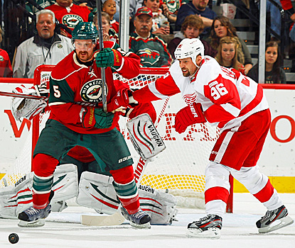 The Red Wings' Tomas Holmstrom battles for the puck with Greg Zanon of the Wild. (Getty Images)