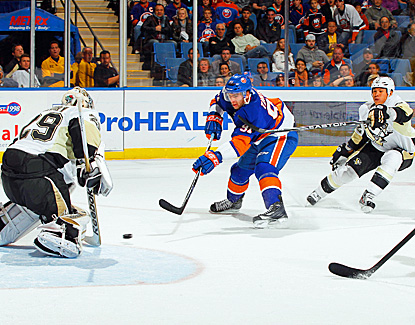 The Penguins' Marc-Andre Fleury (left) makes 33 saves to help defeat the Isles. (Getty Images)