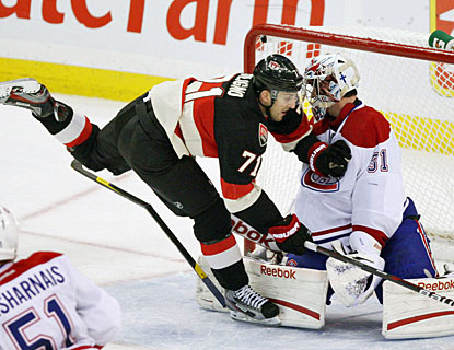 Carey Price, who stops 33 shots, is crashed into by Nick Foligno when the Sens player trips on a broken stick. (AP)