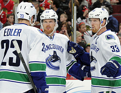 Henrik Sedin (33), who has one goal and threee assists, celebrates with twin brother Daniel and Alexander Edler. (Getty Images)