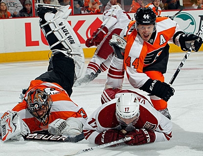Former Coyotes goalie Ilya Bryzgalov is run over by Radim Vrbata as Kimmo Timonen also crashes down. (Getty Images)