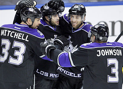 Willie Mitchell is congratulated by Jack Johnson and teammates after scoring the winner for Los Angeles. (AP)