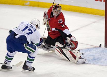 Ryan Kesler, who slips a puck past goalie Craig Anderson, scores twice against the Senators. (AP)