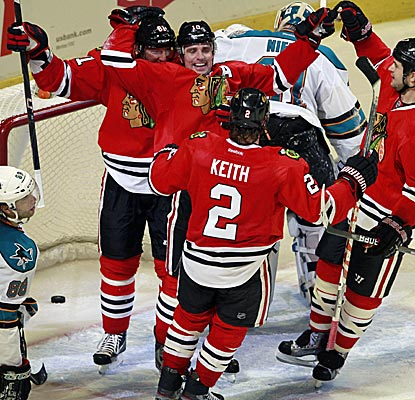 Chicago's Patrick Sharp is swarmed by teammates after he scores the win goal in overtime against the Sharks. (AP)