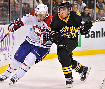 The Bruins' Brad Marchand (right) and the Canadiens' Josh Gorges fight for the puck behind the Habs' goal.  (Getty Images)