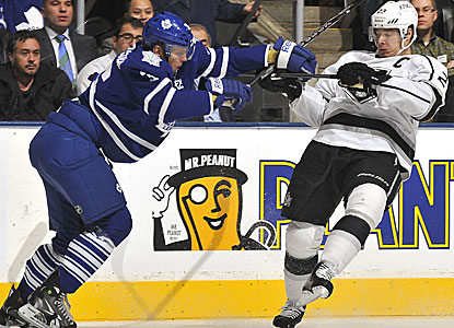 Dustin Brown (right) gets checked by Toronto's Carl Gunnarsson but would score the winner for L.A. in the shootout. (Getty Images)