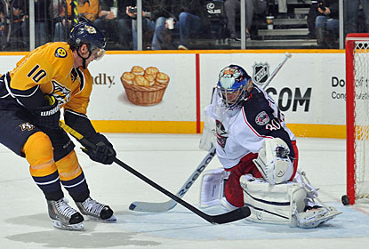 Martin Erat gets the puck past Curtis Sanford after splitting two Blue Jackets defenders. (Getty Images)