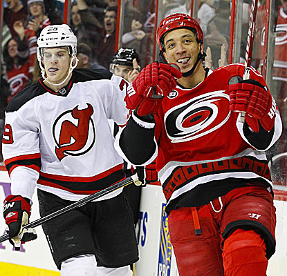 The Hurricanes' Anthony Stewart (right) celebrates his second-period goal in front of the Devils' Mark Fayne. (US Presswire)