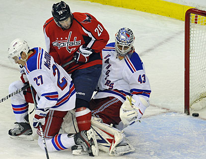 Troy Brouwer is sandwiched between the Rangers goalie and Ryan McDonagh, but is able to redirect the puck in the net. (AP)