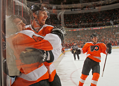 Danny Briere (48) celebrates with teammates after his game-winning goal in OT completes his hat trick. (Getty Images)