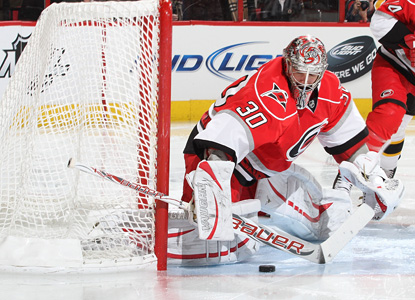 Carolina's Cam Ward makes one of his 33 saves at the net against the defending champion Bruins. (Getty Images)