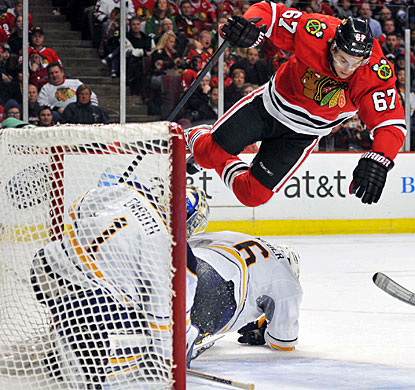 Blackhawks winger Michael Frolik goes airborne to avoid Sabres goalie Jhonas Enroth and defenseman Mike Weber. (US Presswire)