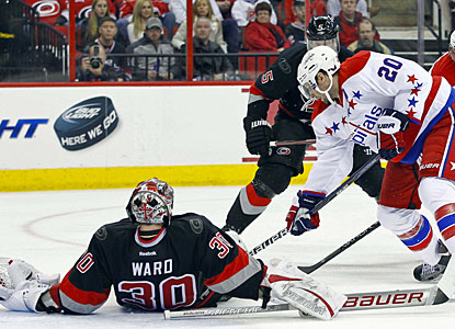 Cam Ward covers the puck to preserve his shutout and help Carolina beat Washington for the first time this season. (US Presswire)
