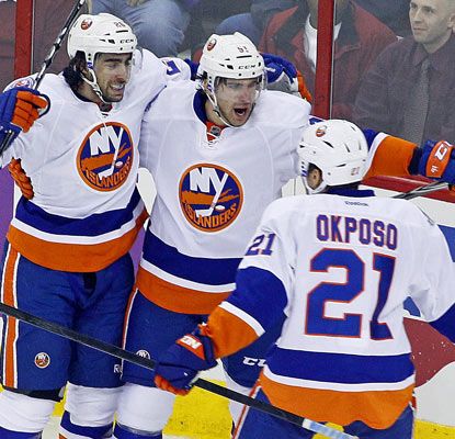 John Tavares (middle) notches four points for the Islanders with two goals and two assists.  (AP)