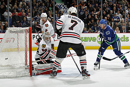 Daniel Sedin (22) scores the winner past Corey Crawford after his brother Henrik finds him open in front. (Getty Images)