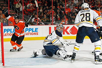Erik Gustafsson scores past Ryan Miller for his first career goal in the NHL. (Getty Images)