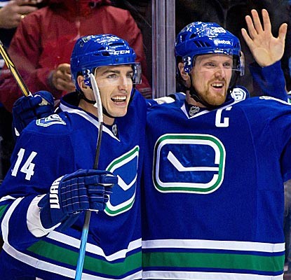 Alex Burrows (left) scores two goals while Henrik Sedin adds four assists in the Canucks' easy win over Toronto.  (AP)