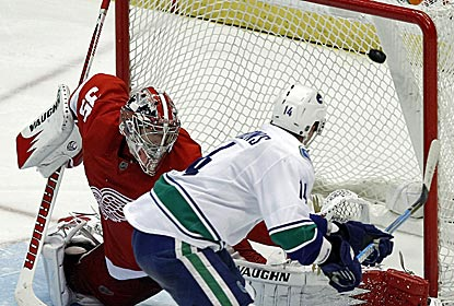 The Canucks' Alex Burrows scores the game-winning shootout goal to end the Red Wings' NHL-record home win streak at 23.  (AP)
