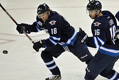 Bryan Little and Andrew Ladd, who scores two goals, control a loose puck in the Jets' big victory over the Lightning.  (Getty Images)