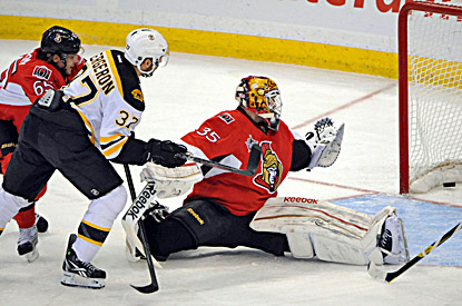 Patrice Bergeron (center) beats Ottawa goaltender Alex Auld for a goal in the first period. (AP)