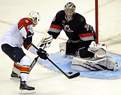 Florida's Stephen Weiss (left) drives into Carolina goalie Justin Peters for the winning goal during a shootout.  (AP)