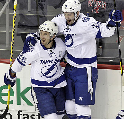 Martin St. Louis celebrates one of his three goals with Teddy Purcell, who contributes a hat trick of assists.  (AP)