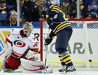 Cam Ward is beaten by a Jason Pominville (not pictured) shot and Thomas Vanek watches the winner hit the net. (US Presswire)