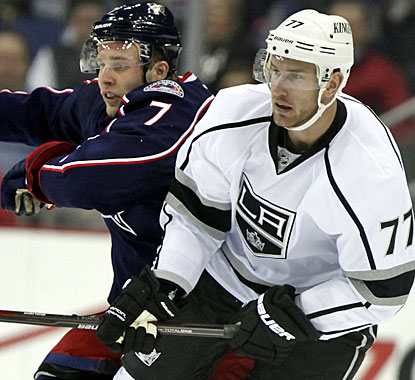 Traded for one another, Jack Johnson battles Jeff Carter. Johnson scores a goal against Los Angeles. (AP)